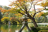 The Kotoji-toro lantern surrounded by orange acer leavers next to Kasumikasumi Pond in the Kenrokuen Garden, Kanazawa, Ishigawa, Japan