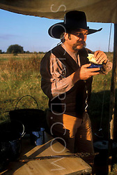 man eating a meal at a campsite