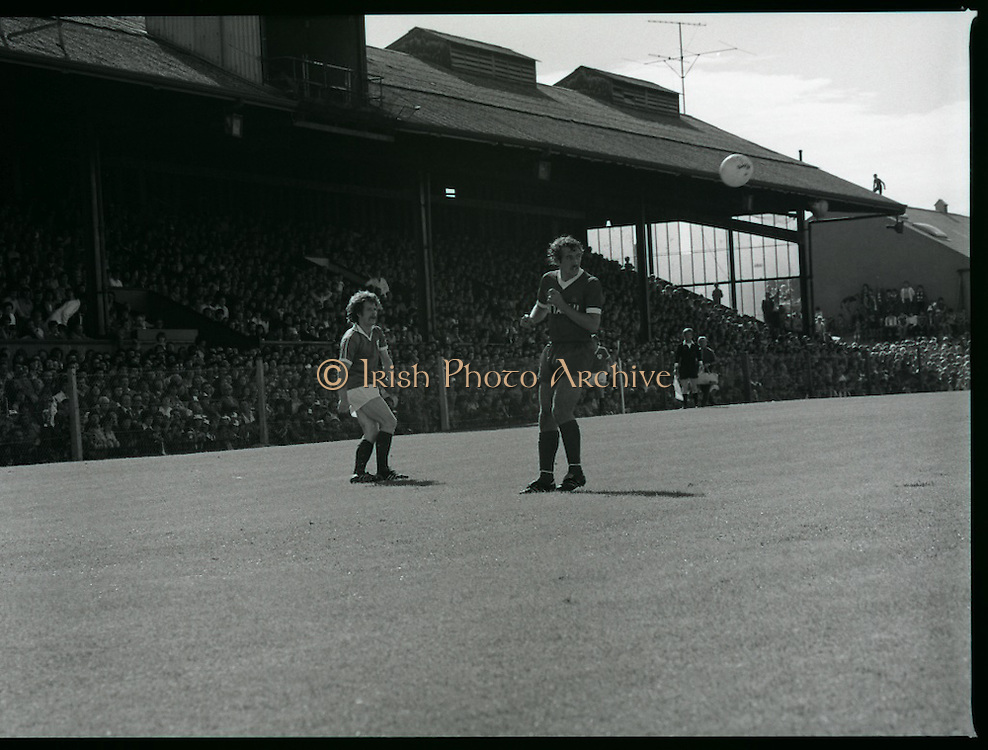 League of Ireland vs Liverpool FC.    (M87)..1979..18.08.1979..08.18.1979..18th August !979..In a pre season friendly the League of Ireland took on Liverpool FC at Dalymount Park Phibsborough,Dublin. The league team was made up of a selection of players from several League of Ireland clubs and was captained by the legendary John Giles. Liverpool won the game by 2 goals to nil..The scorers were Hansen and McDermott...Alan Kennedy is pictured heading clear as an Irish attacker looks on.