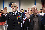 04 JULY 2012 - PHOENIX, AZ:  Sgt. JASON FRITZ, (left) of the US Army, waves an American flag after he was naturalized as a US citizen Wednesday. Fritz, originally from Canada, served in the US Army for more than nine years as a Canadian citizen. About 250 people, from 62 countries, were naturalized as US citizens during the 24th Annual Fiesta of Independence naturization ceremony at South Mountain Community College in Phoenix Wednesday. The ceremony was presided over by the Honorable Roslyn O. Silver, Chief United States District Court Judge.   PHOTO BY JACK KURTZ