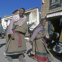 CHINA, TIBET. Tibetan Buddhist pilgrims from remote village circle Jokhang Temple through Lhasa's Barkhor Bazaar.