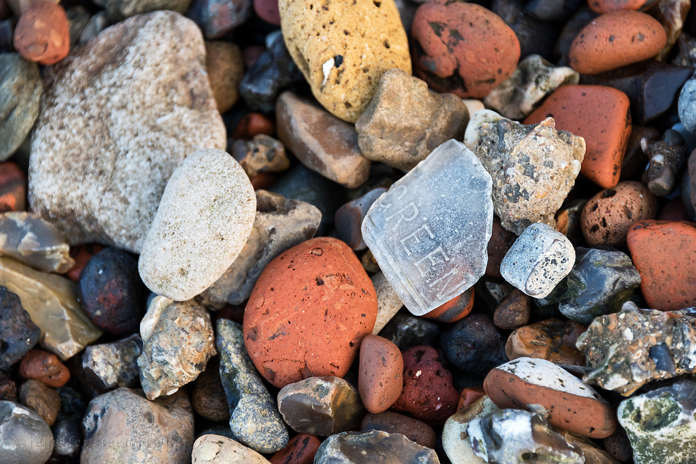 """Sea glass with the embossed word """"green"""" among pieces of red and yellow brick, chalk, and flint on the Greenwich foreshore, London."""