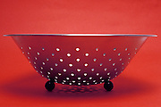 metallic strainer with red background