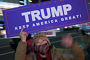 """A Japanese woman, holds a sign reading Trump, Keep America Great as several hundred people, taking part in a """"March For Trump"""" rally  in support of the out-going United States President, Donald Trump. Tokyo, Japan. Wednesday January 6th 2021. The rally of mostly Japanese people took place as part of a similar rally by Trump-supporters in Washington DC as the results of the 2020 US Presidential election were confirmed."""