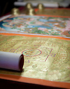 A gold painted thangka laid out on a table.