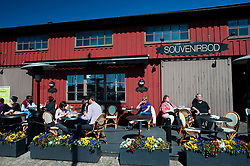 Outdoor bar and cafe in traditional historic red  wooden warehouses and sheds  at Lilla Bommen harbour in Gothenburg Sweden