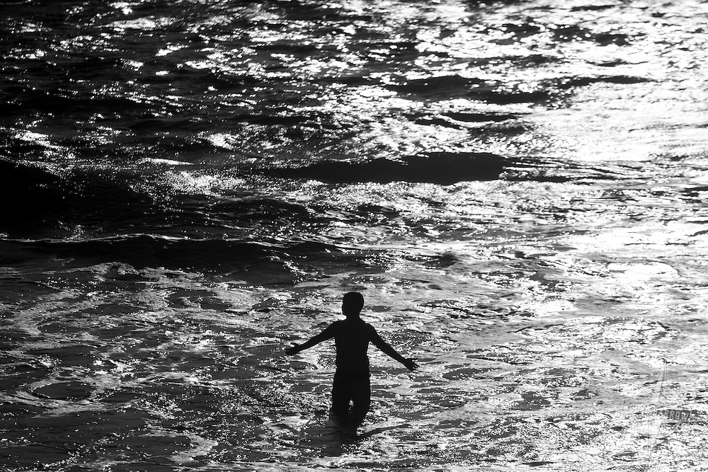Boy standing alone in a dark, silver sea.