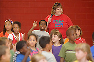 Middletown, NY - A camp counselor smiles and a young boy waves as YMCA summer camp children finish performing a play for their parents in the gymnasium on July 20, 2007..