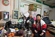"""Couple watching television in a vegetable and fruit shop in Jindo city (Jindo island). Jindo is the 3rd biggest island in South Korea located in the South-West end of the country and famous for the """"Mysterious Sea Route"""" or """"Moses Miracle"""" which is happening during full moon in spring."""