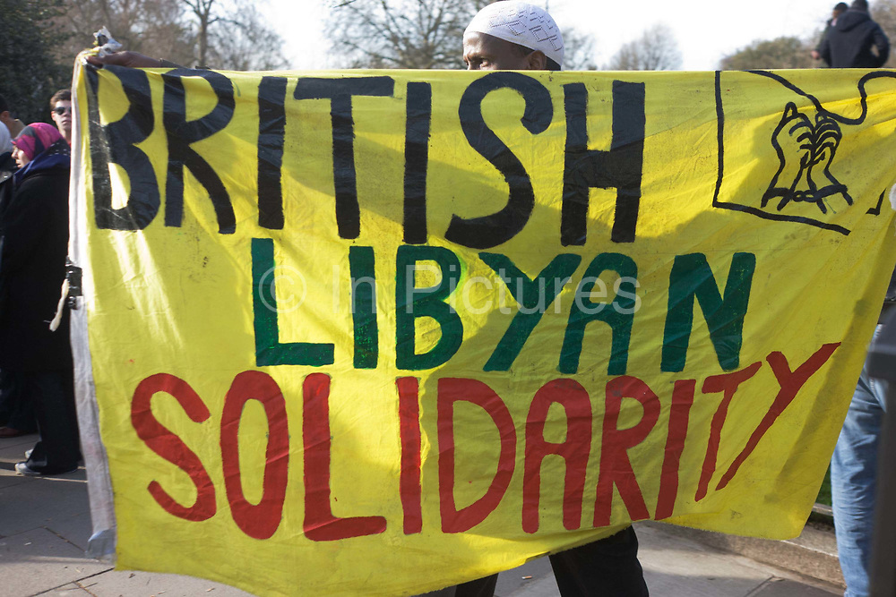 British resident Libyan exiles protest opposite their London embassy against the long-term dictator Muammar al-Gaddafi whose violence has led to a nationwide uprising. The banner reads British Libyan Solidarity with a drawing of bound hands, depicting the oppressive Gaddafi regime, in power after a 42 year coup.