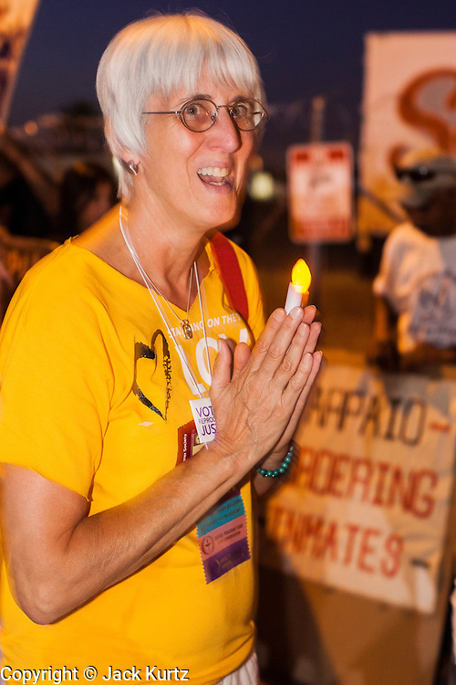 """23 JUNE 2012 - PHOENIX, AZ:   Members of the Unitarian Church march past the Maricopa County Jail in Phoenix. About 2,000 members of the Unitarian Universalist Church, in Phoenix for their national convention, picketed the entrances to the Maricopa County Jail and """"Tent City"""" Saturday night. They were opposed to the treatment of prisoners in the jail, many of whom are not convicted and are awaiting trial, and Maricopa County Sheriff Joe Arpaio's stand on illegal immigration. The protesters carried candles and sang hymns.     PHOTO BY JACK KURTZ"""