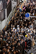 People begin to walk home from Shibuya, some wearing helmets for safety, after a magnitude .9 earthquake hit the Tohoku region of north east Japan causing tremors in Tokyo that stopped the train and cellphone networks. Many people were stranded in the centre of Tokyo over night. Tokyo, Japan Friday March 11th 2011