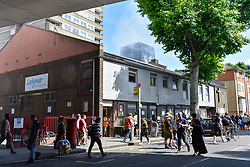 © Licensed to London News Pictures. 14/06/2017. London, UK.   Latymer Road Community Church, seen in the foreground, acts as a drop off point for donations of clothing for those displaced by the fire.  The Grenfell Tower near Latimer Road in west London smoulders after it was engulfed in a huge fire the previous night, resulting in at least twelve fatalities with many more in critical condition. Photo credit : Stephen Chung/LNP
