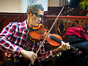 """24 DECEMBER 2017 - HANOI, VIETNAM:  A violinist plays """"Silent Night"""" before Christmas Eve services in St. Joseph's Cathedral in Hanoi. The commercial and gift giving aspect of Christmas is widely celebrated in Vietnam and Vietnam's 5+ million Catholics celebrate the religious aspects of Christmas.    PHOTO BY JACK KURTZ"""