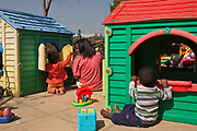 A school girl volunteer plays with babies and toddlers in the play garden toy houses at Princess Alice's Adoption home which is a children's home in association with Bigshoes Foundation, Johannesburg, South Africa.