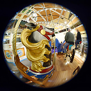 Garden City, New York, USA. March 9, 2019.  Carousel riders on ornate carved wood horses, seen in fisheye lens view, enjoy free rides during Unveiling Ceremony of Nunley's Carousel mural, held at historic Nunley's Carousel in its Pavilion on Museum Row on Long Island.
