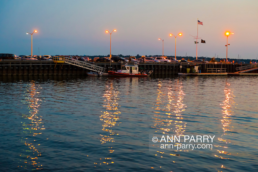 Port Washington, New York, U.S. - July 11, 2014 - Golden sunset comes to Manhasset Bay, with boats docked at pier and reflections of lights shimmering on water, on the North Shore village on Long Island Gold Coast.