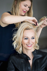 Hairdresser combing fashion models hair at salon