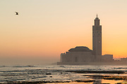 Rough sea and Hassan II Mosque at foggy sunset in Casablanca, Morocco