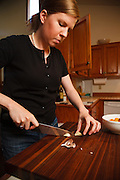 USA, Oregon, Eugene, young woman chopping garlic for bruschetta. MR