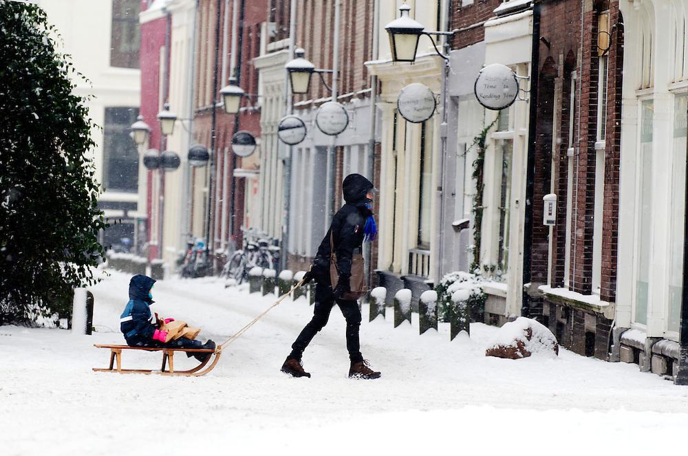 Een vrouw loopt met een kind op de slee achter haar aan in de sneeuw over de Oudegracht in Utrecht.<br /> <br /> A woman is walling with a child on a sled at the Oudegracht in Utrecht.
