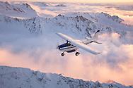 A Homer Air cessna 206 flies over fog enshrouded mountain ridges during a flightsee from Homer, Alaska.