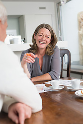 Couple with construction plans sitting at table
