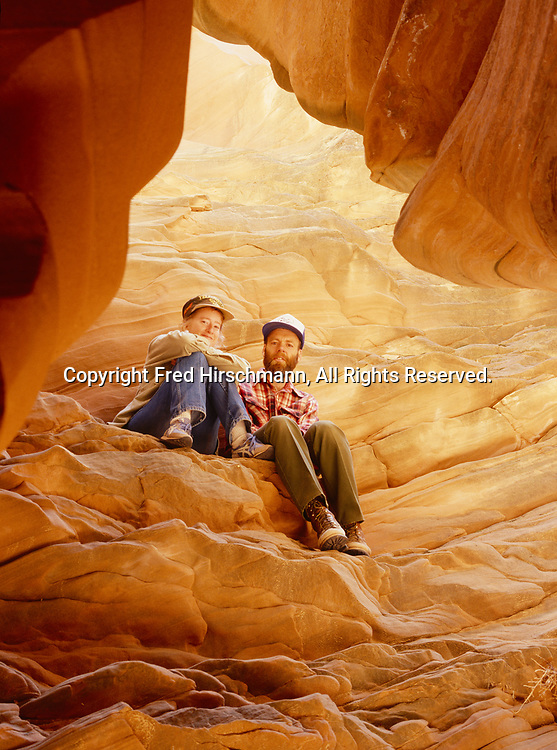 Mary Kline and Rick Hutchinson sitting on a sandstone ledge within a slot canyon, Colorado Plateau, Arizona.