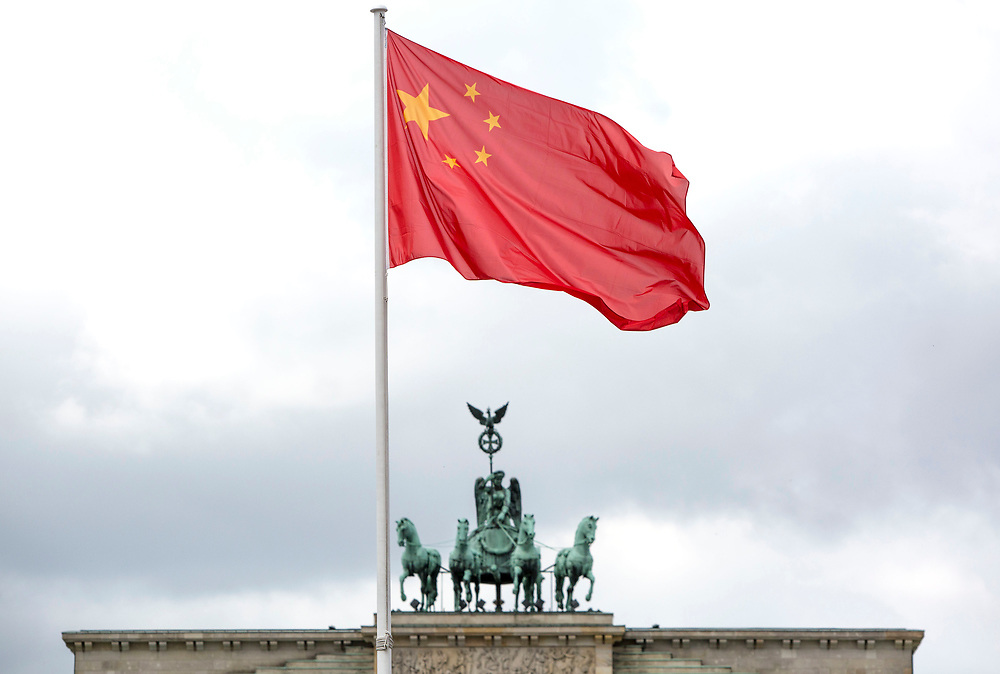 The Chinese flag is seen raised over Parizer Platz in Berlin during a visit of the Chinese President Xi Jinping in the city , with the Brandenburg Gate seen in the background, on July 5, 2017.
