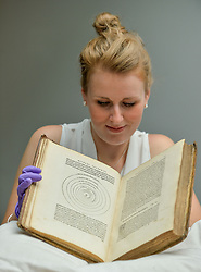Pictured: Curator of the exhibition Kirsty MacNab with a rare first edition of Nicolaus Copernicus' book from 1543 where he proposed the theory of the earth revolving round the sun.<br /> <br /> An exhibition at the University of Edinburgh main library entitle 'Astronomy Victorious: understanding our Universe' runs from 27 July till 27 October 2018.<br /> <br /> © Dave Johnston / EEm