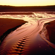 The sun sets of the outgoing tide at the Parker River National Wildlife Refuge on Plum Island, Newbury, Massachusetts