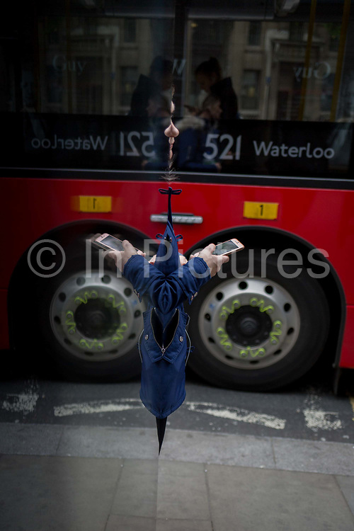 A symmetrical reflection of a lady using her phone at a bus stop in the Strand in central London, on 4th May 2017, in London, England.