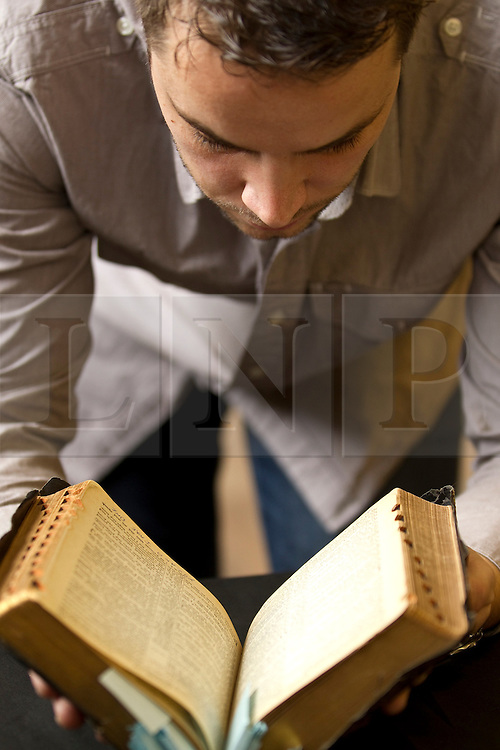 © Licensed to London News Pictures . 07/09/2012 . Manchester , UK . A personalised bible , given to Elvis Presley by his Uncle Vester and Aunt Clettes for Christmas in 1957 , which goes up for auction tomorrow (8th September) in Stockport . Omega Auction House auctioneer, Paul Fairweather , examines the lot . The bible is expected to fetch £20,000 . It will be auctioned alongside other pieces of Elvis memorabilia , including a pair of the King's underpants . Photo credit : Joel Goodman/LNP