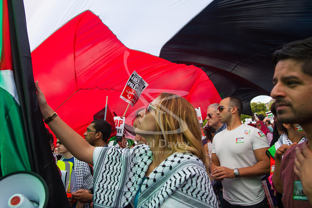 London, August 9th 2014. Protesters listen to speeches under a giant Palestinian flag as tens of thousands attend a rally in support of the people of Palestine.