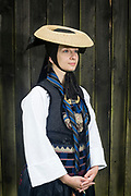 Ann Kristin is wearing a traditional Vierländer Bridesmaid Costume in Neuengamme in Hamburg, Germany on June 25, 2017.<br /> <br /> <br /> Men already abandoned the traditional clothing after the war after 1870. Women wore the traditional dresses until after WWI. During and after the war, women sold their dresses and costumes to women from the city of Hamburg who wore the dresses to the markets. Vierlande always stood for good quality, so people dressed up on the markets with Vierländer Costumes to push the value of their products. Even the company Rama advertised their margarine products with a picture of a young women in traditional Vierländer Costume in the beginning of 1900.