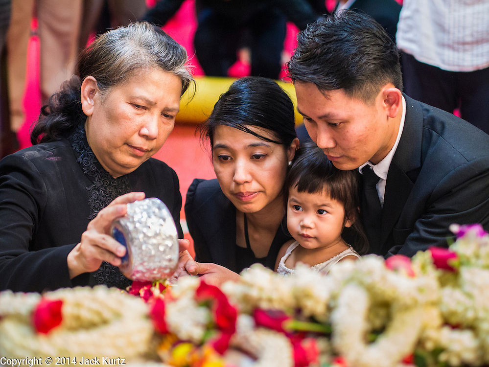 12 OCTOBER 2104 - BANG BUA THONG, NONTHABURI, THAILAND: RATCHANEE WIRIYACHAI, (left) widow of Apiwan Wiriyachai, and other family members pour scented water over the hand of Apiwan Wiriyachai on the first day of Apiwan's funeral rites at Wat Bang Phai in Bang Bua Thong, a Bangkok suburb, Sunday. Apiwan was a prominent Red Shirt leader, member of the Pheu Thai Party of former Prime Minister Yingluck Shinawatra, and a member of the Thai parliament. The military government that deposed the elected government in May, 2014, charged Apiwan with Lese Majeste for allegedly insulting the Thai Monarchy. Rather than face the charges, Apiwan fled Thailand to the Philippines. He died of a lung infection in the Philippines on Oct. 6. The military government gave his family permission to bring him back to Thailand for the funeral. He will be cremated later in October. The first day of the funeral rites Sunday drew tens of thousands of Red Shirts and their supporters, in the first Red Shirt gathering since the coup.    PHOTO BY JACK KURTZ