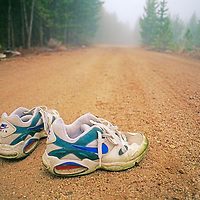 A runner's shoes wait to be used on a foggy road in the Wind River Mountains.