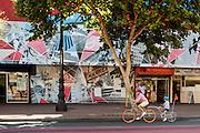 Een vrouw fietst met een kindje op de fietsaanhanger over Market Street in San Francisco. De Amerikaanse stad San Francisco aan de westkust is een van de grootste steden in Amerika en kenmerkt zich door de steile heuvels in de stad. Ondanks de heuvels wordt er steeds meer gefietst in de stad.<br /> <br /> A woman cycles with a child on a bike trailer at Market Street in San Francisco. The US city of San Francisco on the west coast is one of the largest cities in America and is characterized by the steep hills in the city. Despite the hills more and more people cycle.