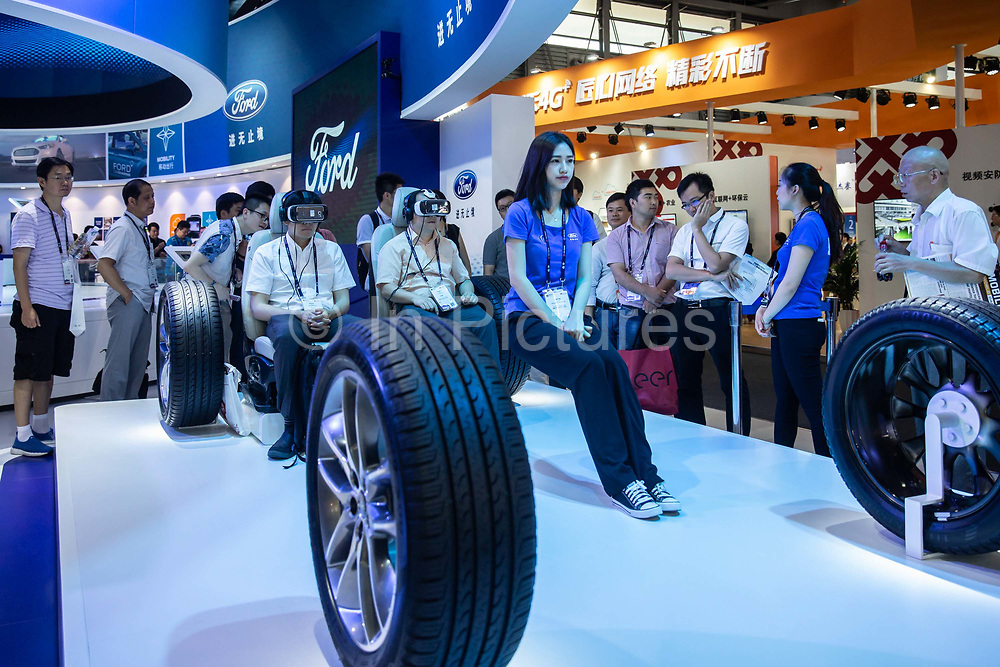 Attendees try virtual reality VR goggles as an attendant sits on a supporting bar at a Ford Motors Co. booth at the Mobile World Congress Shanghai in Shanghai, China, on Wednesday, June 29, 2016.