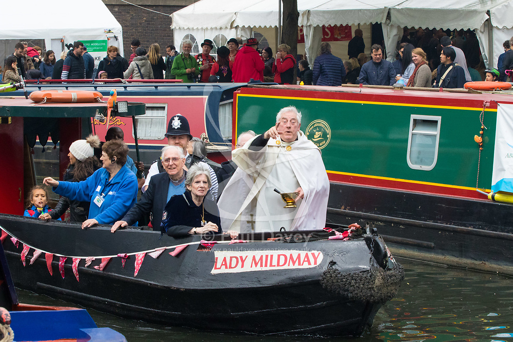 Little Venice, London, April 30th 2017. Narrowboaters from all over the UK gather for the annual Canalway Cavalcade, held on the May Day Bank holiday weekend, organised by the Inland Waterways Association, where boaters get the chance to display their immaculately prepared and brightly painted craft as well as compete in various manoeuvring tests. PICTURED: Father Gary Bradley of the Parish of Little Venice sprinkles Holy Water as he blesses the boats.