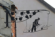 A wrought iron painted sign that illustrates the theme of champagne and wine production: black sign showing a man doing pruning and training of the vines and a vine with leafs and grape bunches, backlit, the village of Hautvillers in Vallee de la Marne, Champagne, Marne, Ardennes, France