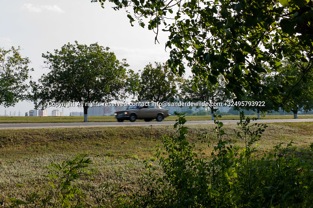 20150828  Moldova, Transnistria,Pridnestrovian Moldavian Republic (PMR) Tiraspol. a Lada drives by at the east side of tiraspol,with lots of appartment buildings, flats in the background.