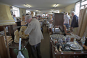 People looking around an auction room prior to a sale of secondhand items, Suffolk, England