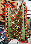Woven rugs are sold Otavalo, Ecuador, South America. The culturally vibrant town of Otavalo attracts many tourists to a valley of the Imbabura Province of Ecuador, surrounded by the peaks of Imbabura 4,610m, Cotacachi 4,995m, and Mojanda volcanoes. The indigenous Otavaleños are famous for weaving textiles, usually made of wool, which are sold at the famous Saturday market and smaller markets during the rest of the week. The Plaza del Ponchos and many shops tantalize buyers with a wide array of handicrafts. Nearby villages and towns are also famous for particular crafts: Cotacachi, the center of Ecuador's leather industry, is known for its polished calf skins; and San Antonio specializes in wood carving of statues, picture frames and furniture. Otavaliña women traditionally wear distinctive white embroidered blouses, with flared lace sleeves, and black or dark over skirts, with cream or white under skirts. Long hair is tied back with a 3cm band of woven multi colored material, often matching the band which is wound several times around their waists. They usually have many strings of gold beads around their necks, and matching tightly wound long strings of coral beads around each wrist. Men wear white trousers, and dark blue ponchos. Otavalo is also known for its Inca-influenced traditional music (sometimes known as Andean New Age) and musicians who travel around the world.