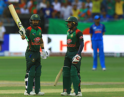 September 28, 2018 - Dubai, United Arab Emirates - Bangladesh cricketer Liton Das celebrates after 50 runs as Mehidy Hasan Miraz looks on  during the final cricket match of Asia Cup 2018  between India and Bangladesh at Dubai International cricket stadium,Dubai, United Arab Emirates. 09-28-2018  (Credit Image: © Tharaka Basnayaka/NurPhoto/ZUMA Press)