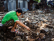21 MARCH 2017 - BANGKOK, THAILAND: A boy who lives in Pom Mahakan uses a kitchen spoon to dig in the wreckage of a home destroyed by city officials during the forced evictions of Pom Mahakan residents. He was looking for old coins and anything salvageable. The final evictions of the remaining families in Pom Mahakan, a slum community in a 19th century fort in Bangkok, have started. City officials are moving the residents out of the fort. NGOs and historic preservation organizations protested the city's action but city officials did not relent and started evicting the remaining families in early March.               PHOTO BY JACK KURTZ
