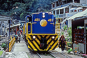 "A blue and yellow PeruRail train stops in Aguas Calientes village (""Machupicchu Town""), at the foot of Machu Picchu in the Cordillera Vilcabamba, Andes mountains, Peru, South America. PeruRail runs passenger train service from Cusco to Aguas Calientes (Spanish for ""hot water"" or ""hot springs""), nestled on the Urubamba/Vilcanota River (Sacred Valley of the Incas). Machu Picchu was built around 1450 AD as an estate for the Inca emperor Pachacuti (14381472). Spaniards passed in the river valley below but never discovered Machu Picchu during their conquest of the Incas 1532-1572. The outside world was unaware of the ""Lost City of the Incas"" until revealed by American historian Hiram Bingham in 1911. Machu Picchu perches at 2430 meters elevation (7970 feet) on a well defended ridge 450 meters (1480 ft) above a loop of the Urubamba/Vilcanota River (Sacred Valley of the Incas). UNESCO honored the Historic Sanctuary of Machu Picchu on the World Heritage List in 1983."