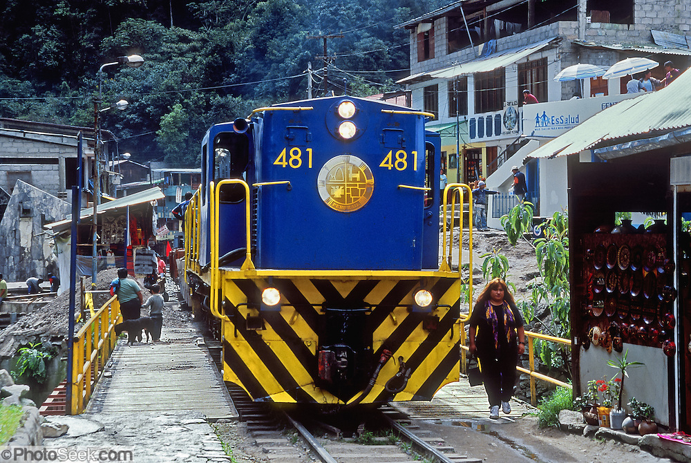"""A blue and yellow PeruRail train stops in Aguas Calientes village (""""Machupicchu Town""""), at the foot of Machu Picchu in the Cordillera Vilcabamba, Andes mountains, Peru, South America. PeruRail runs passenger train service from Cusco to Aguas Calientes (Spanish for """"hot water"""" or """"hot springs""""), nestled on the Urubamba/Vilcanota River (Sacred Valley of the Incas). Machu Picchu was built around 1450 AD as an estate for the Inca emperor Pachacuti (14381472). Spaniards passed in the river valley below but never discovered Machu Picchu during their conquest of the Incas 1532-1572. The outside world was unaware of the """"Lost City of the Incas"""" until revealed by American historian Hiram Bingham in 1911. Machu Picchu perches at 2430 meters elevation (7970 feet) on a well defended ridge 450 meters (1480 ft) above a loop of the Urubamba/Vilcanota River (Sacred Valley of the Incas). UNESCO honored the Historic Sanctuary of Machu Picchu on the World Heritage List in 1983."""