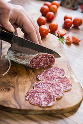 Person's hand chopping sausage with knife, Germany