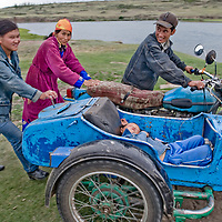 MONGOLIA, Darhad Valley. Family waits for ferry for their motorcycle - with a sidecar carrying their baby - across the Shishgit River, north of Tsaagan Nuur.
